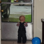 Isaac looking out the front door in his overalls, April 17, 2009.